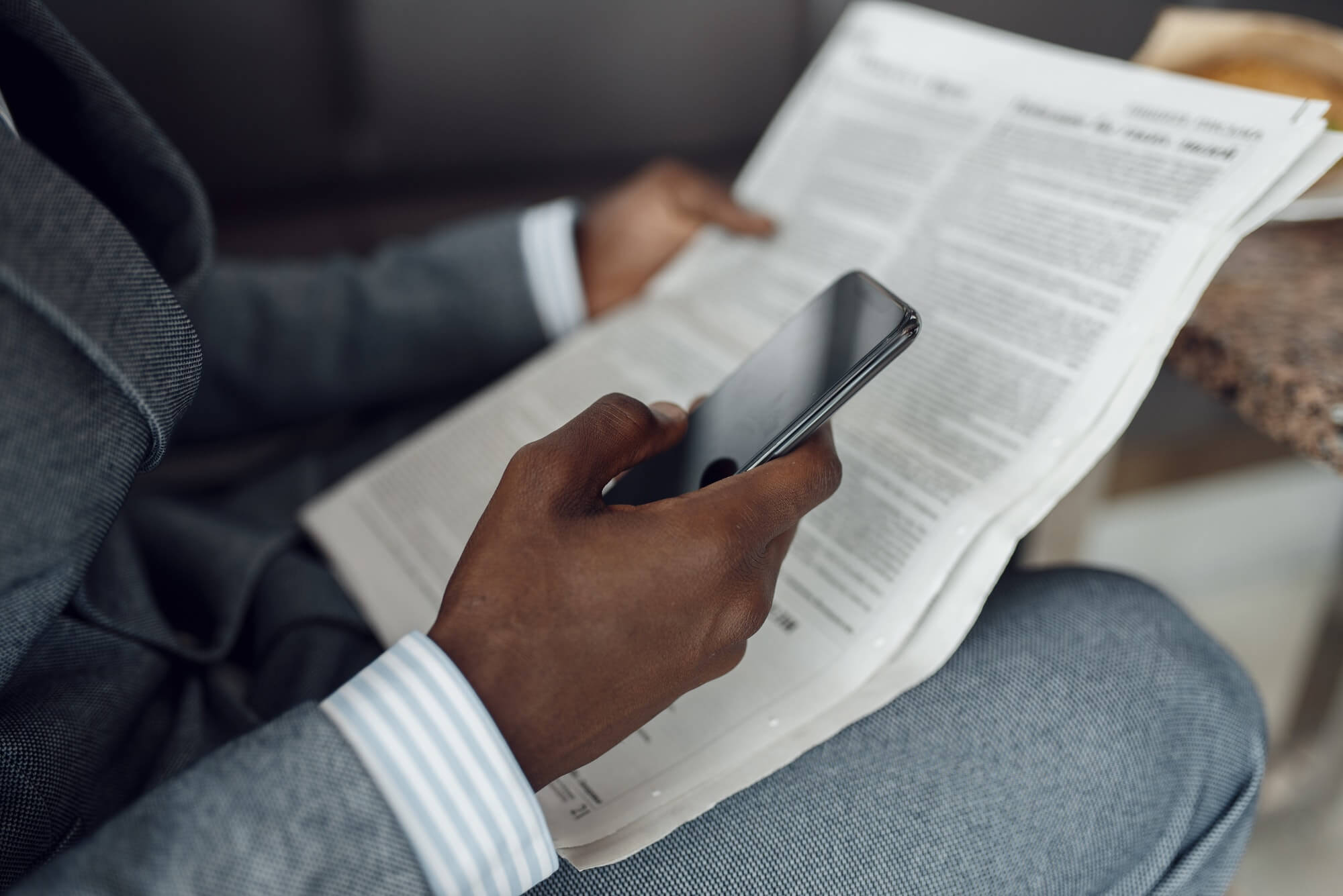 Ebony businessman hands with newspaper and phone